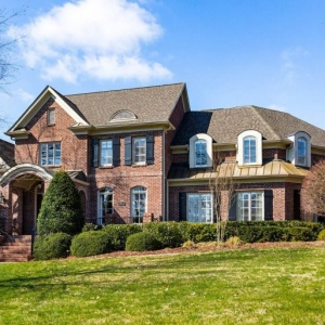 large custom brick home with brown gray roof shingles and a brown metal roof accents tan trim and black shutters