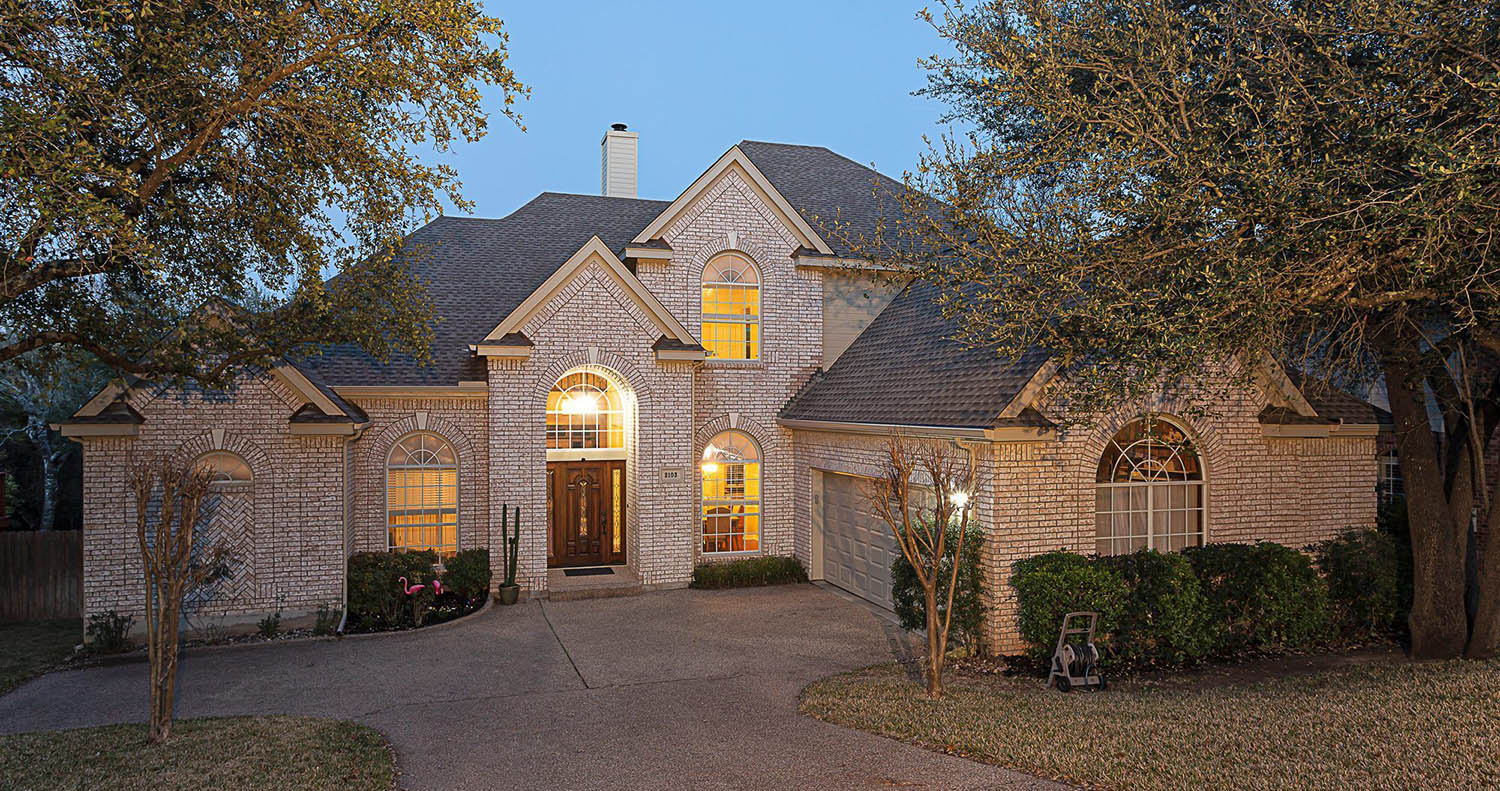 Light colored brick home with medium brown front door.