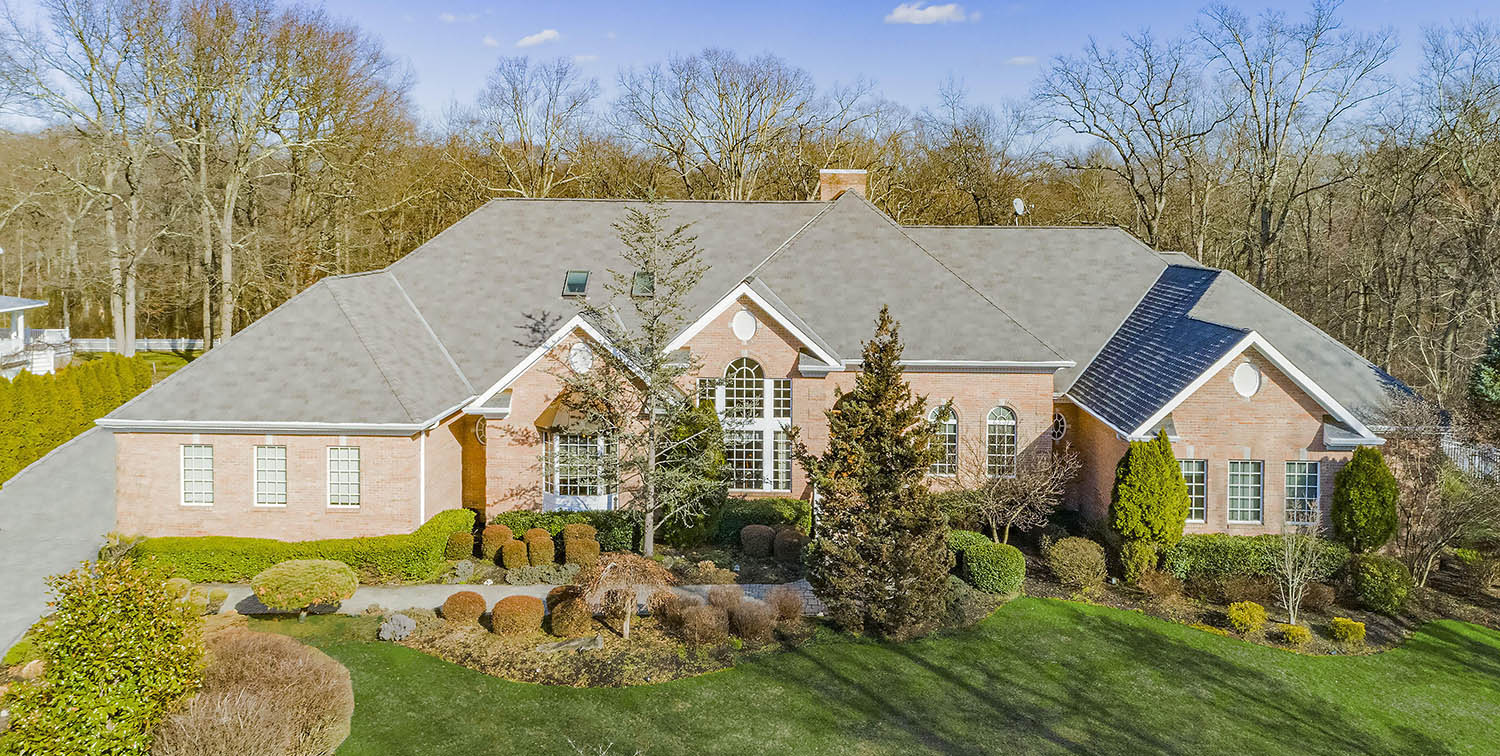 large red brick ranch style home with a dark gray roof shingle. Black metal accent roofing. Beautiful green landscaping.
