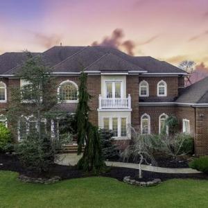 Beautiful custom red brick home with dark gray shingle roof. Tan stucco veneer. White trim. Green landscaping.