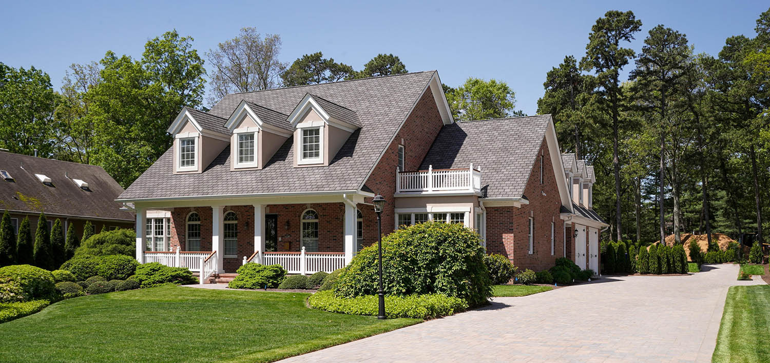 Red brick ranch home design. Gray brown roof color with dormers. White columns, trim and railings with wood hand rail. White garage doors.