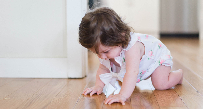 radiant floor heating systems baby girl sitting on a hardwood floor