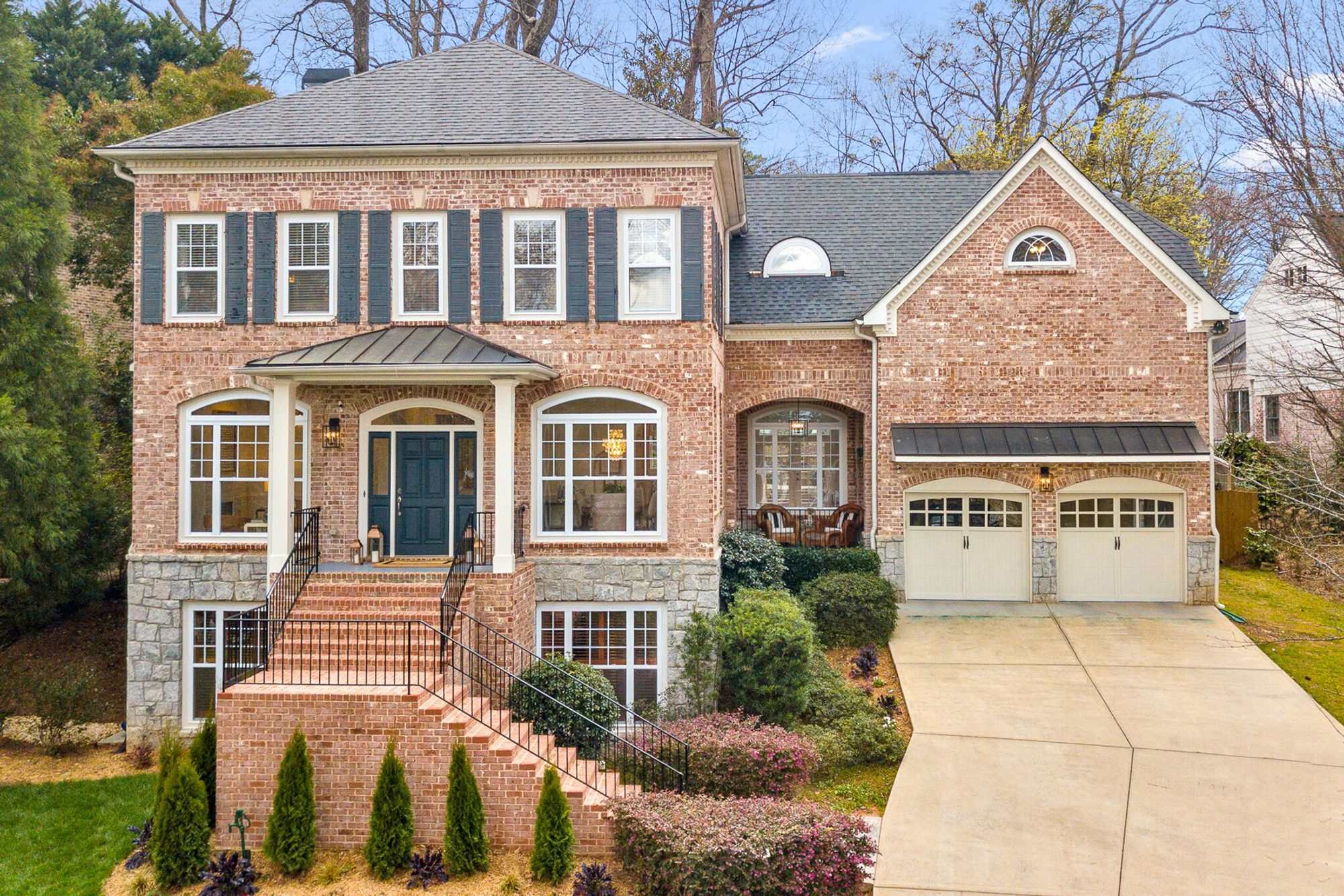 red brick home with a stone foundation, metal accent roofing and black shutters.