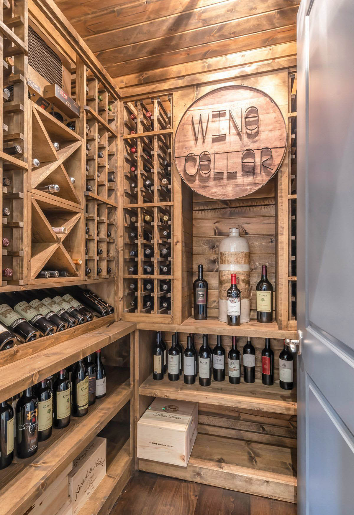 Small rustic wine room with custom wood racks and shelves.
