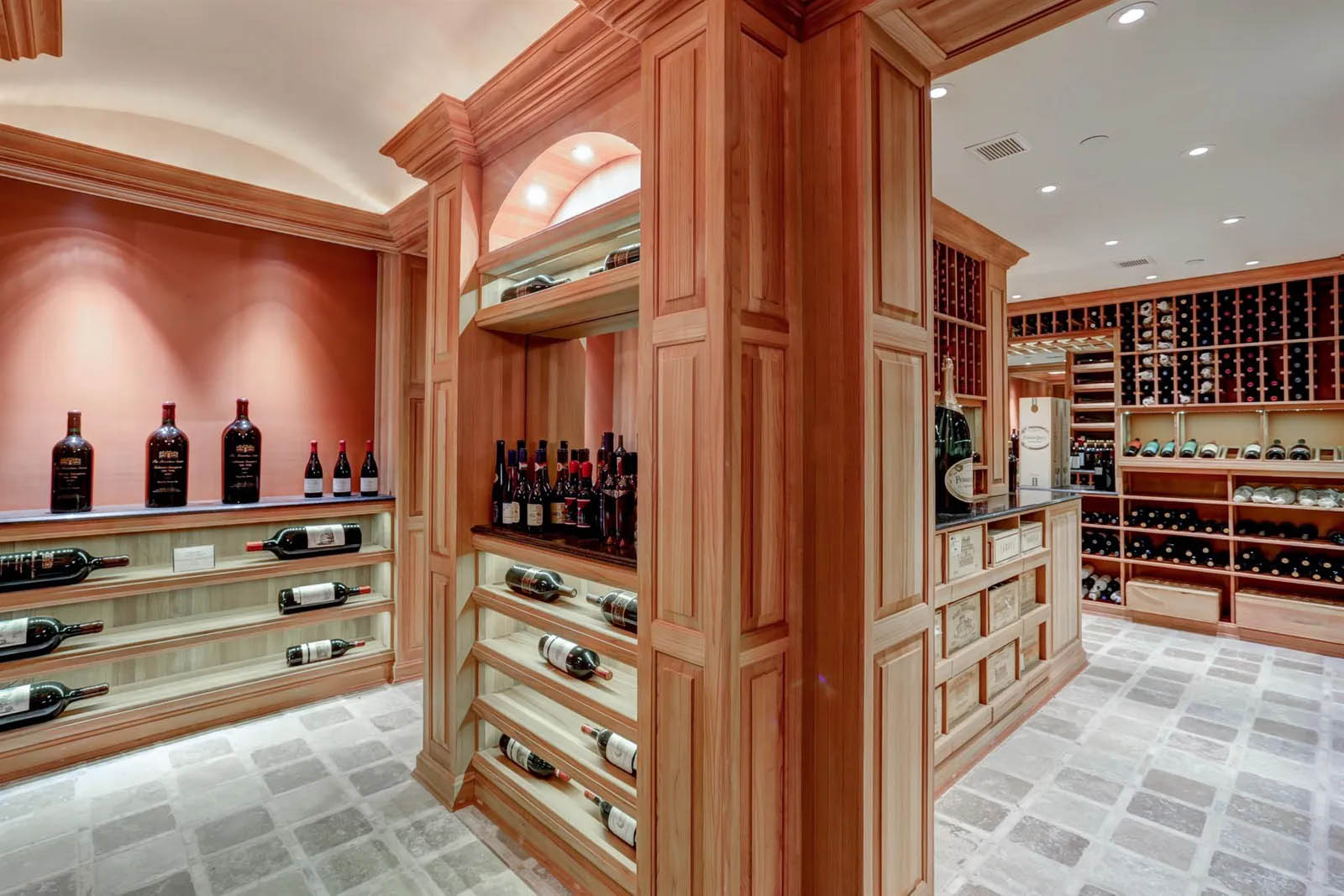 Large wine room featuring custom wood racks and shelves.
