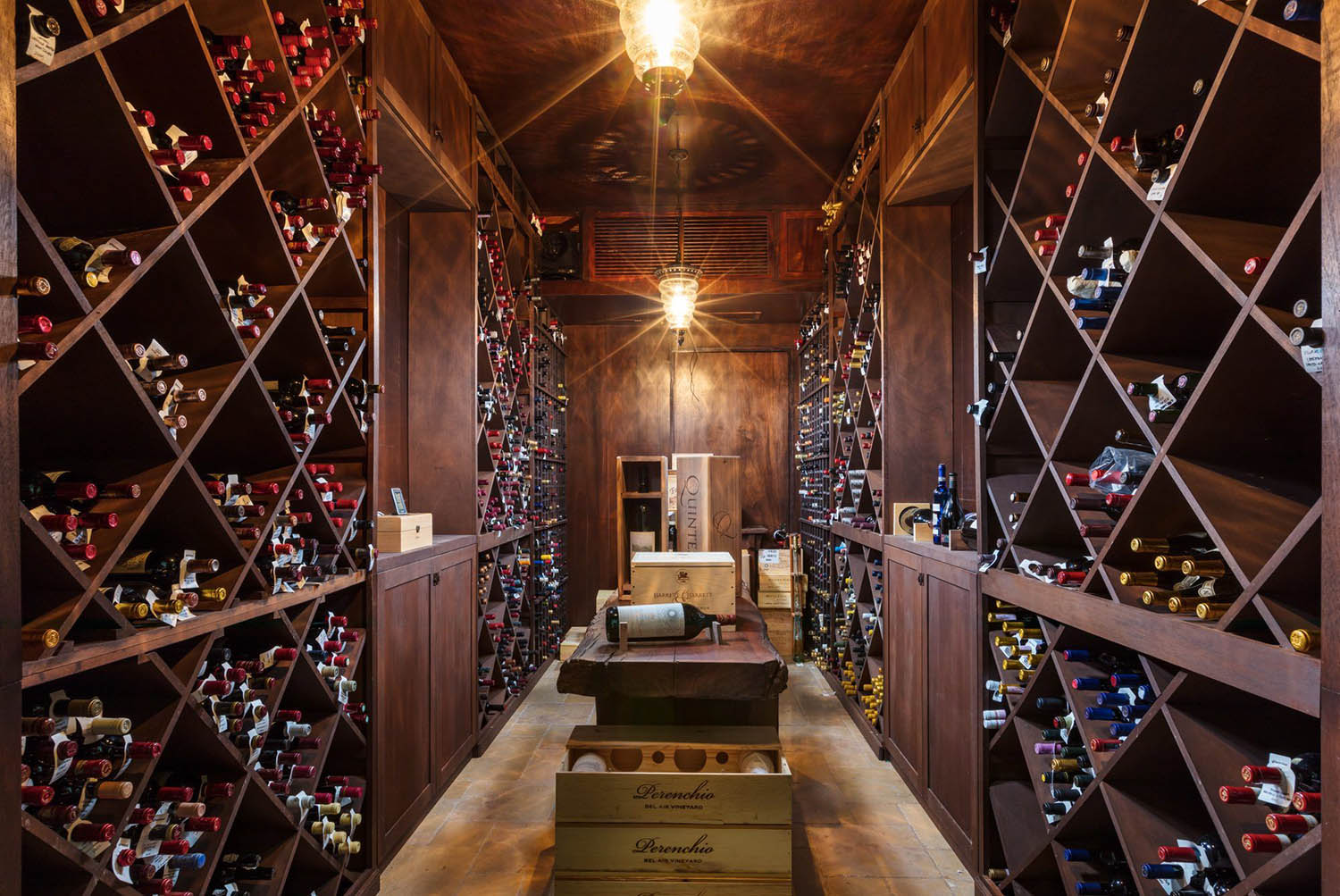 Wine cellar with a variety of storage designs. Individual, diamond and square storage racks with countertop, shelves and center barrel.