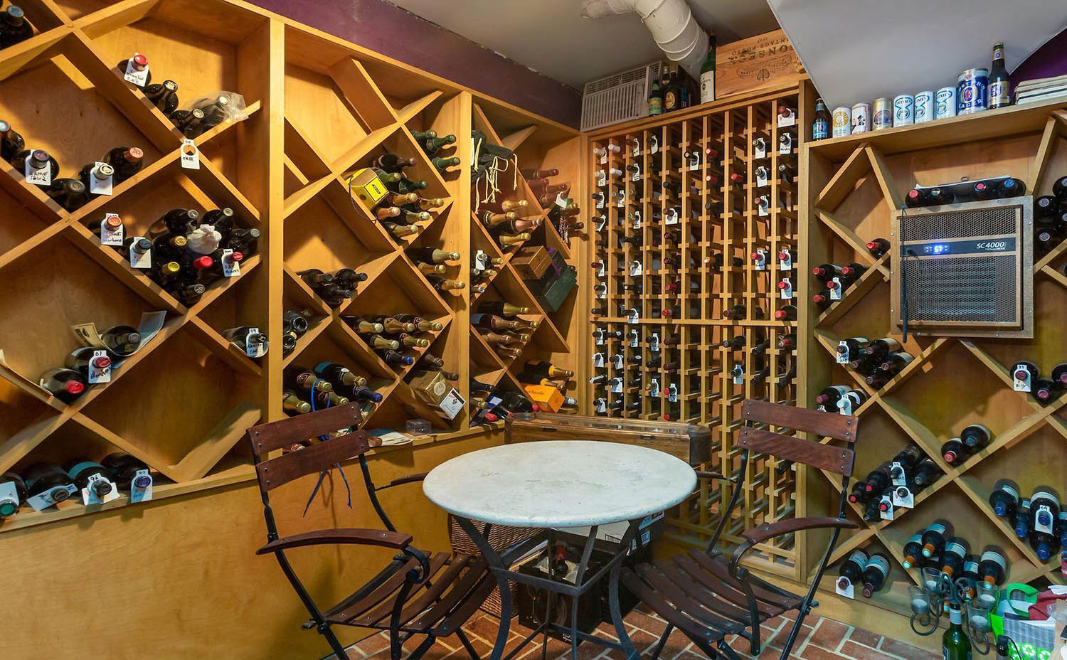 DIY wine cellar with wood racks and table with wall cooling unit