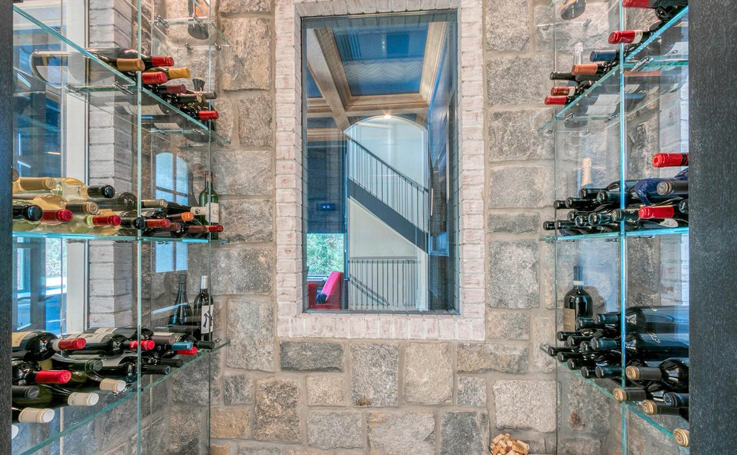 contemporary wine room with glass shelves and stone walls
