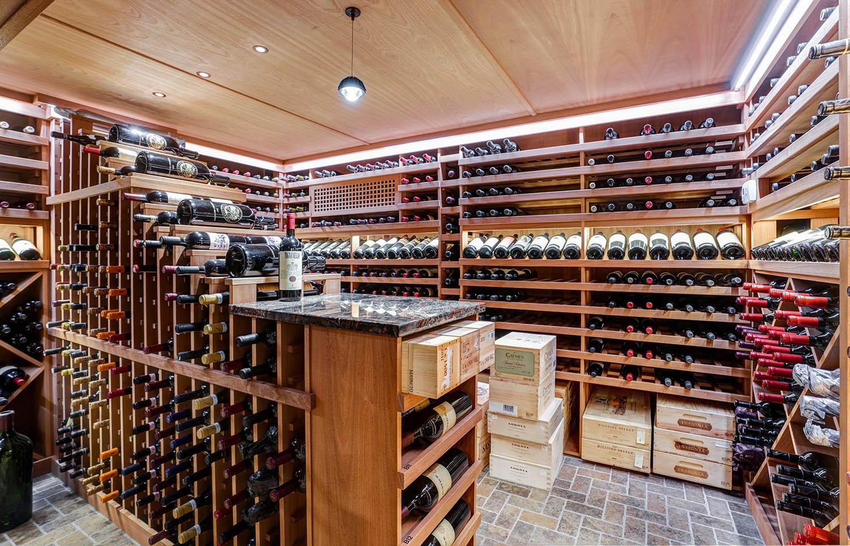 wine cellar with wood paneling wood racks and brick floor