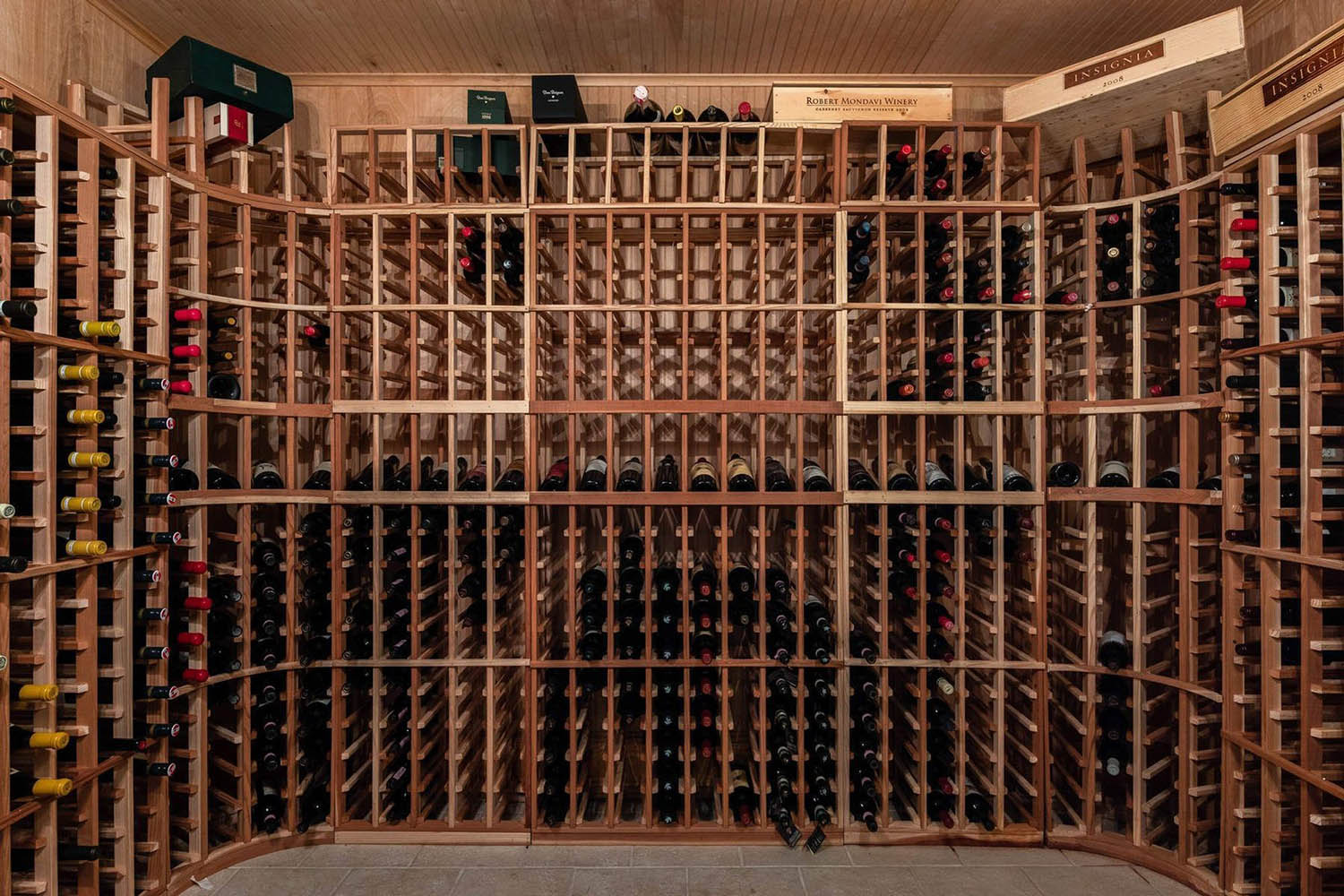 Large DIY wine room with wooden single bottle racks. Wood wall paneling.