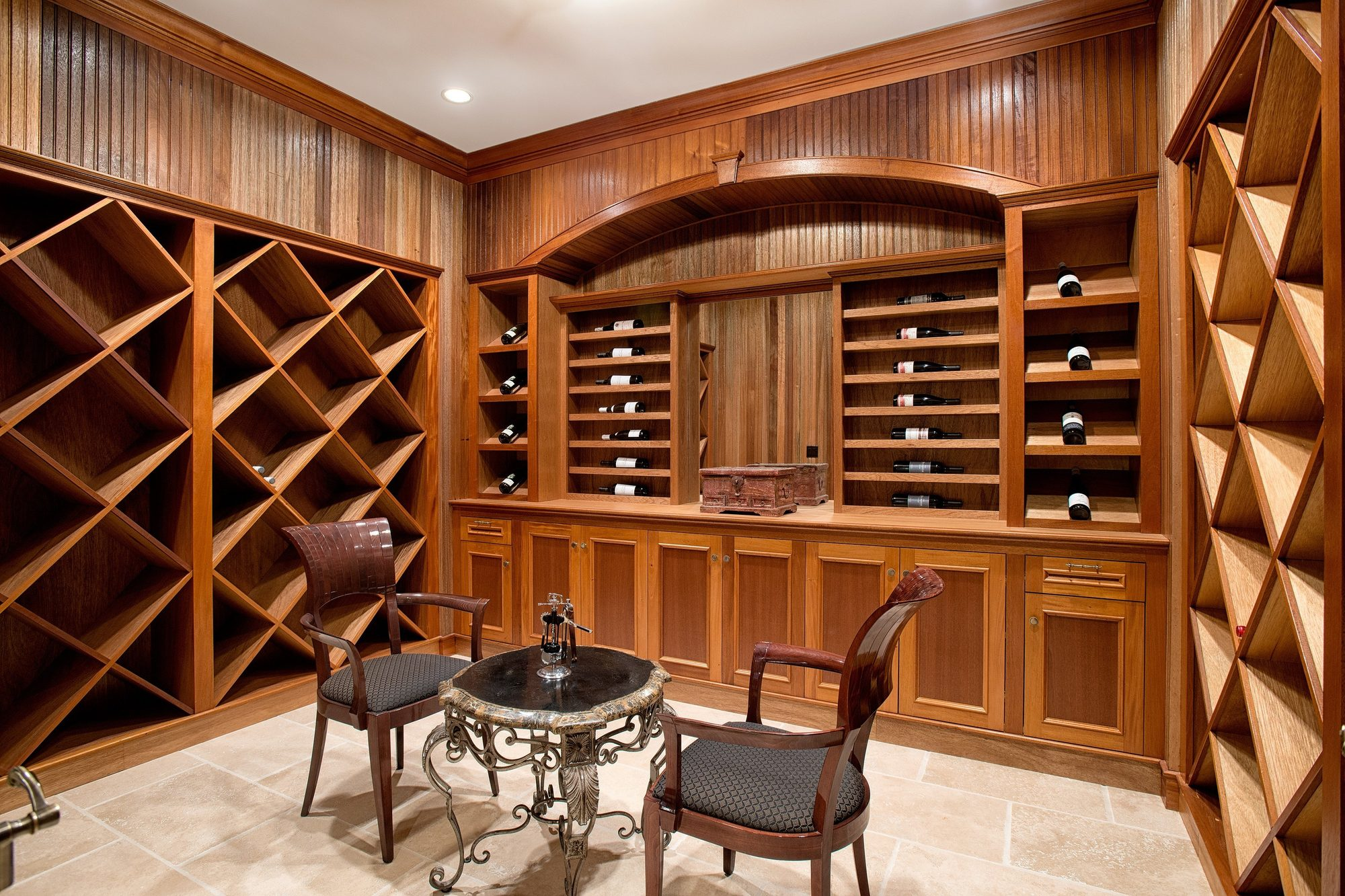 Beautiful wine room featuring custom built racks, shelves and drawers. Medium stained real wood. Stone tile floors. Vertical wall paneling.