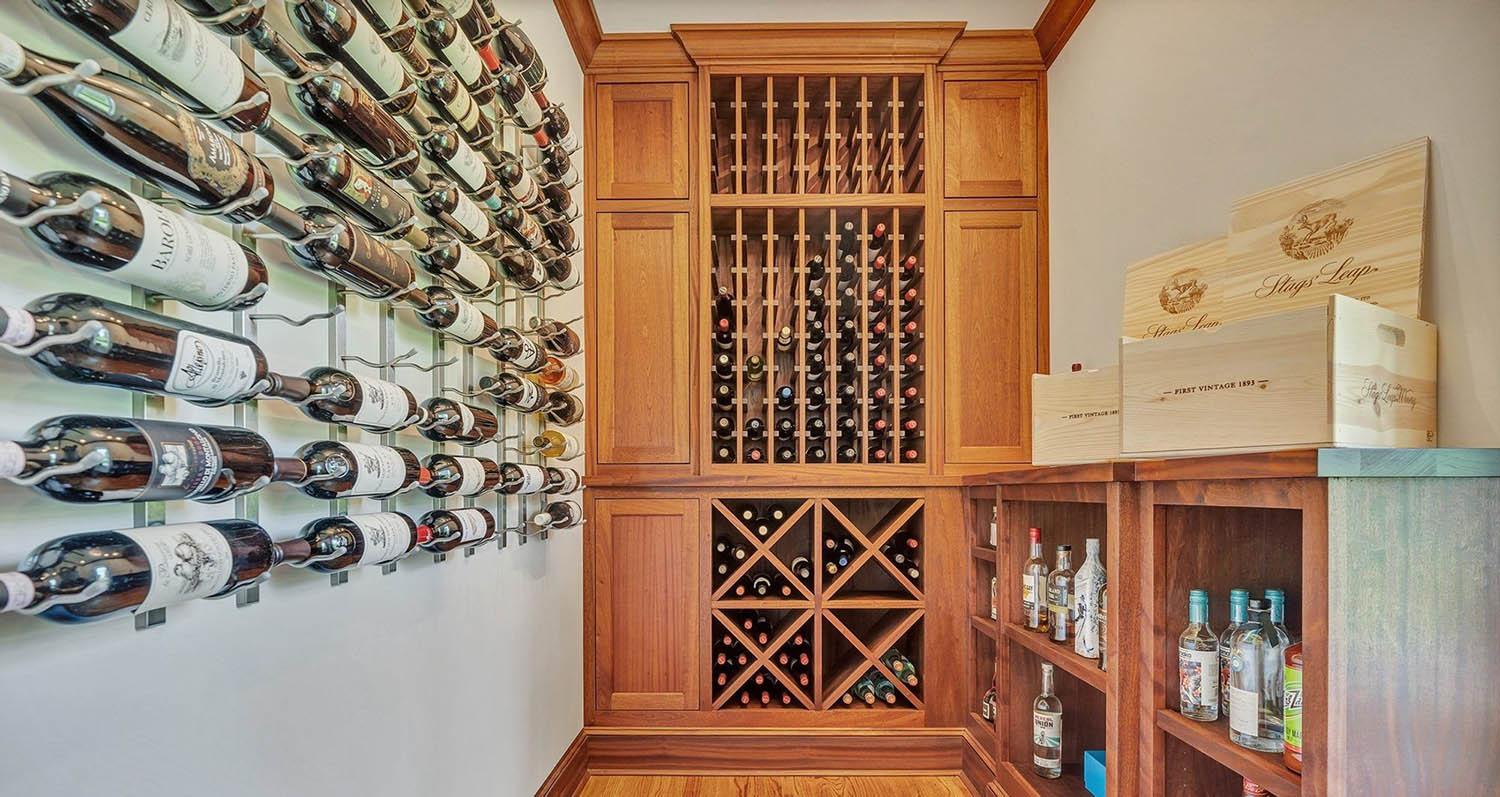 Simple DIY wine room with wood cabinets and shelving. Metal wall racks.