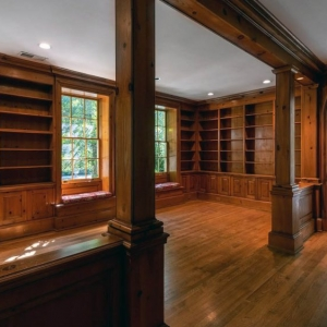 Rustic wood wall paneling with matching hardwood floors. White ceilings. Arched doorsways.