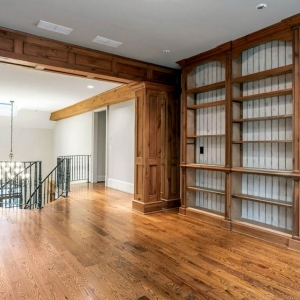 Rustic knotty wood paneling with a natural finish. Matching hardwood floors. Built in shelves.