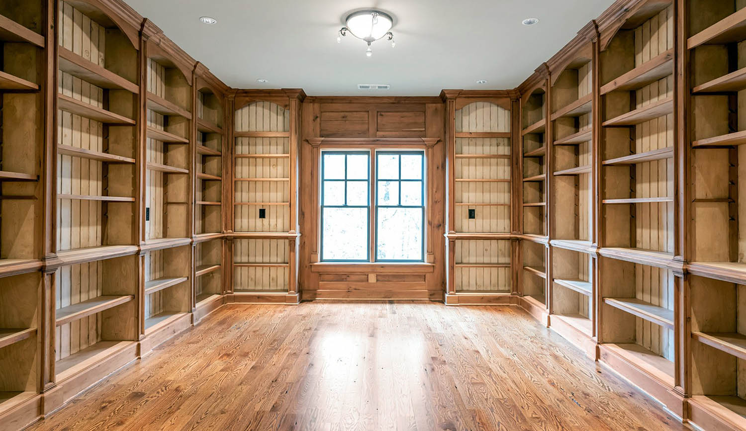 Library / office with all wood wall paneling and built in shelving. Matching hardwood floors. White ceiling.