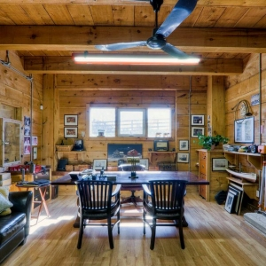 Rusticbarn office with wood walls, ceiling and floors. Red brick accent wall with wood burning stove.