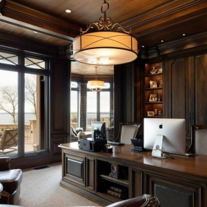 Beautiful home office with dark wood wall paneling. Built ins. Large wood desk. Beige carpet.