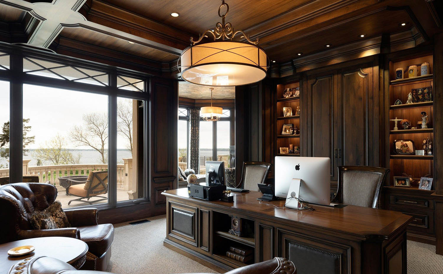 All dark wood office with wood wall paneling and wood ceiling. Matching wood desk. Tan carpeting. Large windows let in tons of natural light.