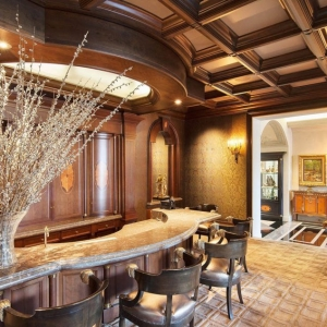 Home bar with real wood coffered ceiling. Stained wood beams with brown coffers. Wallpapered walls with wood trim.