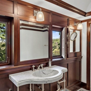Bathroom with wood wall paneling and marble. White ceiling. Marble sink with chrome.