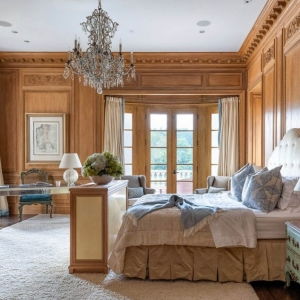 Master bedroom with woodwall paneling, custom trim and thick crown molding. Hardwood floors with an area rug.