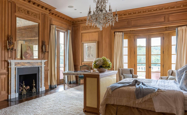 All wood master bedroom walls with wood burning fireplace. Wood floors. Custom trim.