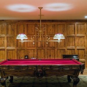 Billiard room with wood wall paneling. Beautiful wood pool table with red felt. Wood floors.