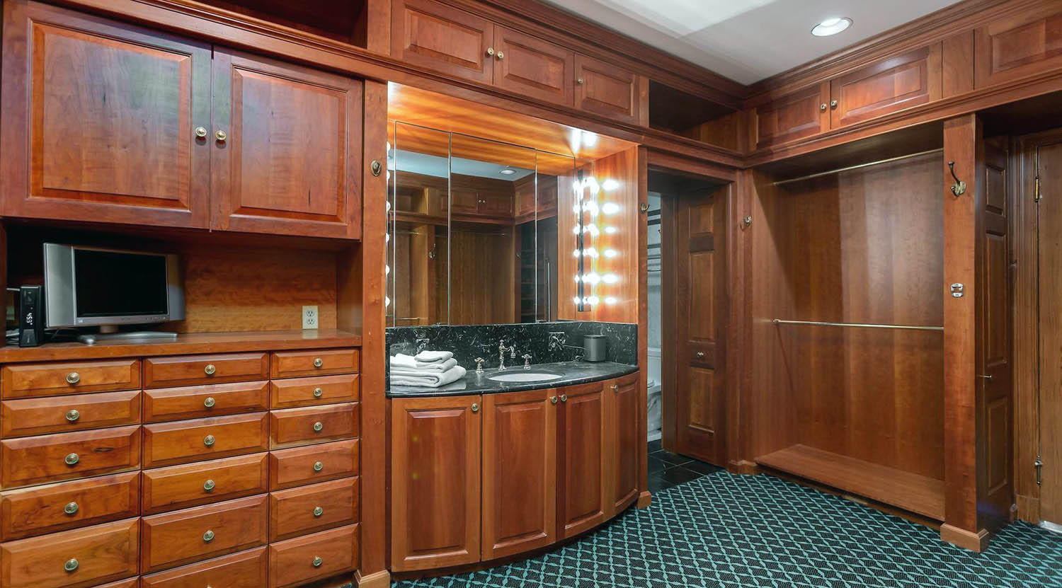 Walk in closet with all wood walls and built ins with green carpet.