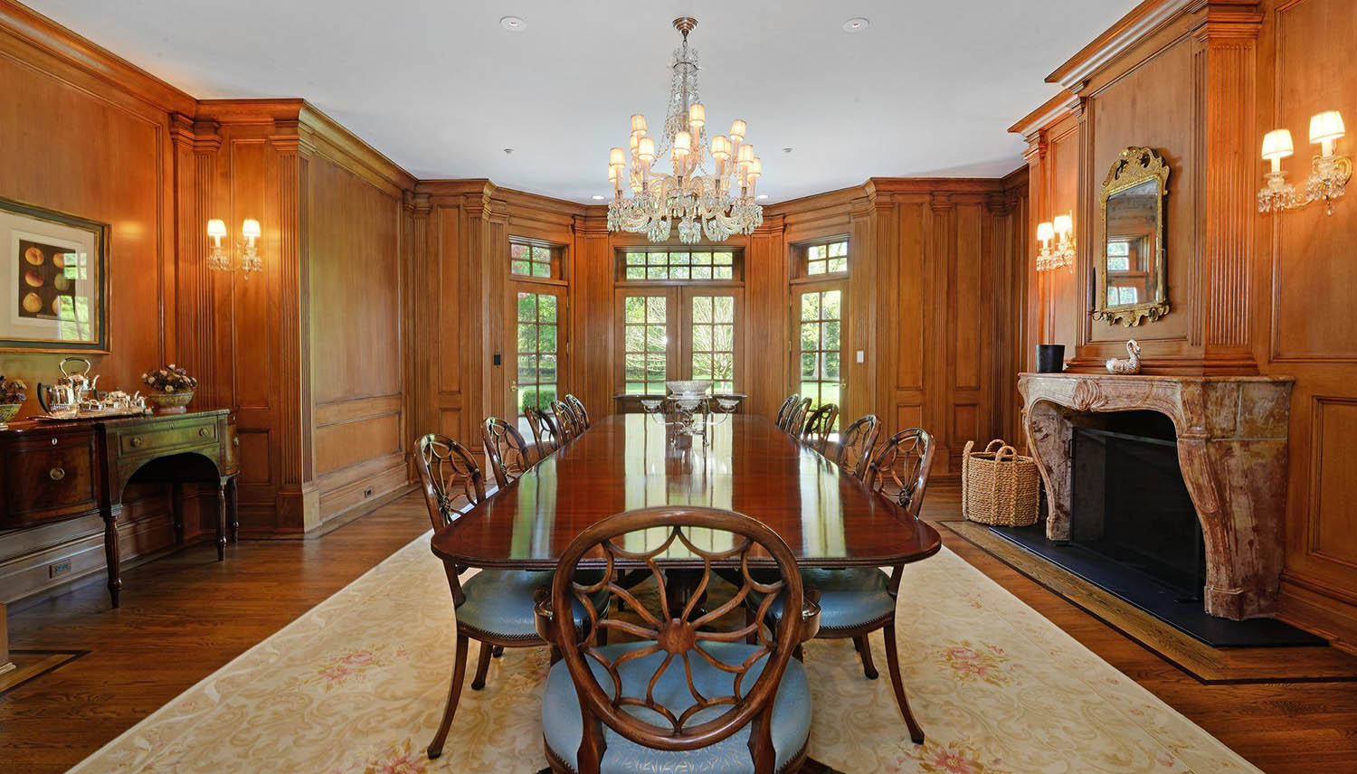 Dining room. All wood walls with custom trim and crown molding. Large dining table.