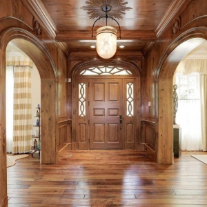 Hallway with all wood wall paneling and matching hardwood floors. Wood ceiling.