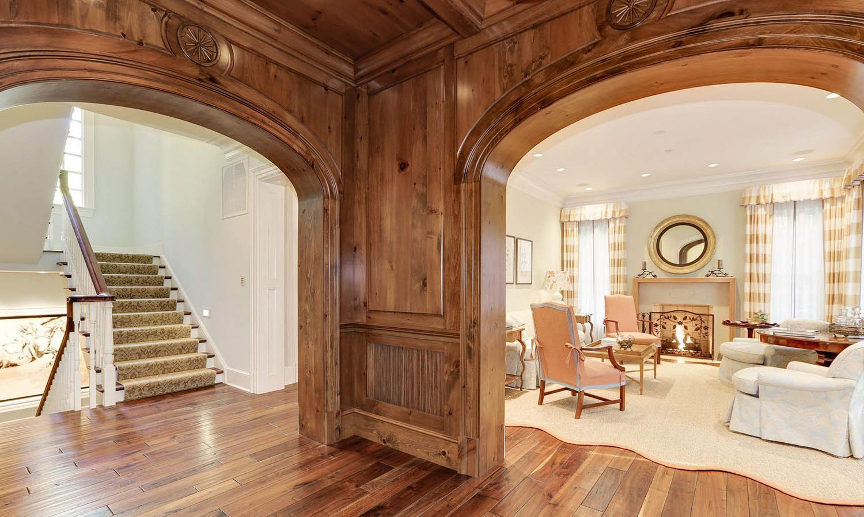All wood wall paneling. Wood hallway with matching hardwood floors. Medium brown stain.
