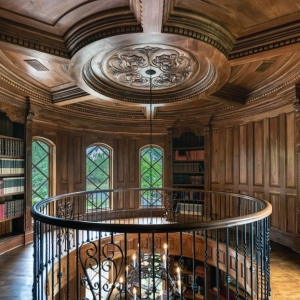 Beautiful round home library with wood walls and custom trim and wall paneling. Round coffered ceiling with real wood.