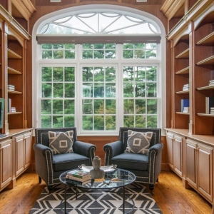 Library / office with all wood walls, built in shelving and cabinets. Huge window with white frame.