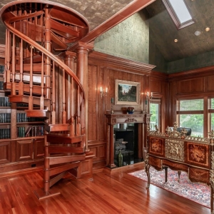 home library / office with all wood walls and matching floors. Reddish brown stain. Spiral staircase.