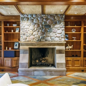 Room with all wood walls and ceiling. Real stone fireplace surround. Custom wood built ins.
