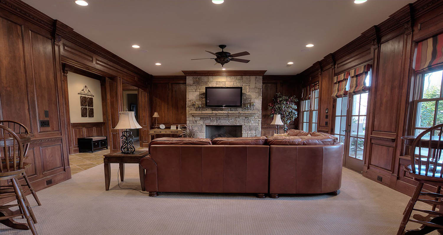 Living room with all wood walls, beige carpet and white ceiling. Brown leather sofa. Stone fireplace.