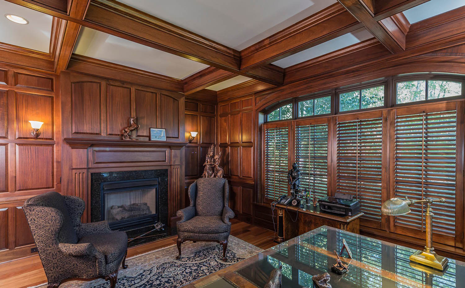 Wood walls with matching coffered ceiling. Gas fireplace with black granite surround. Hardwood floors and area rug and glass desk.