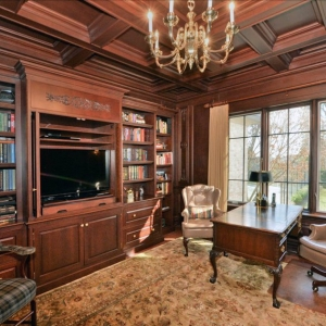 Home office with wood walls stained medium brown with matching all wood coffered ceiling.