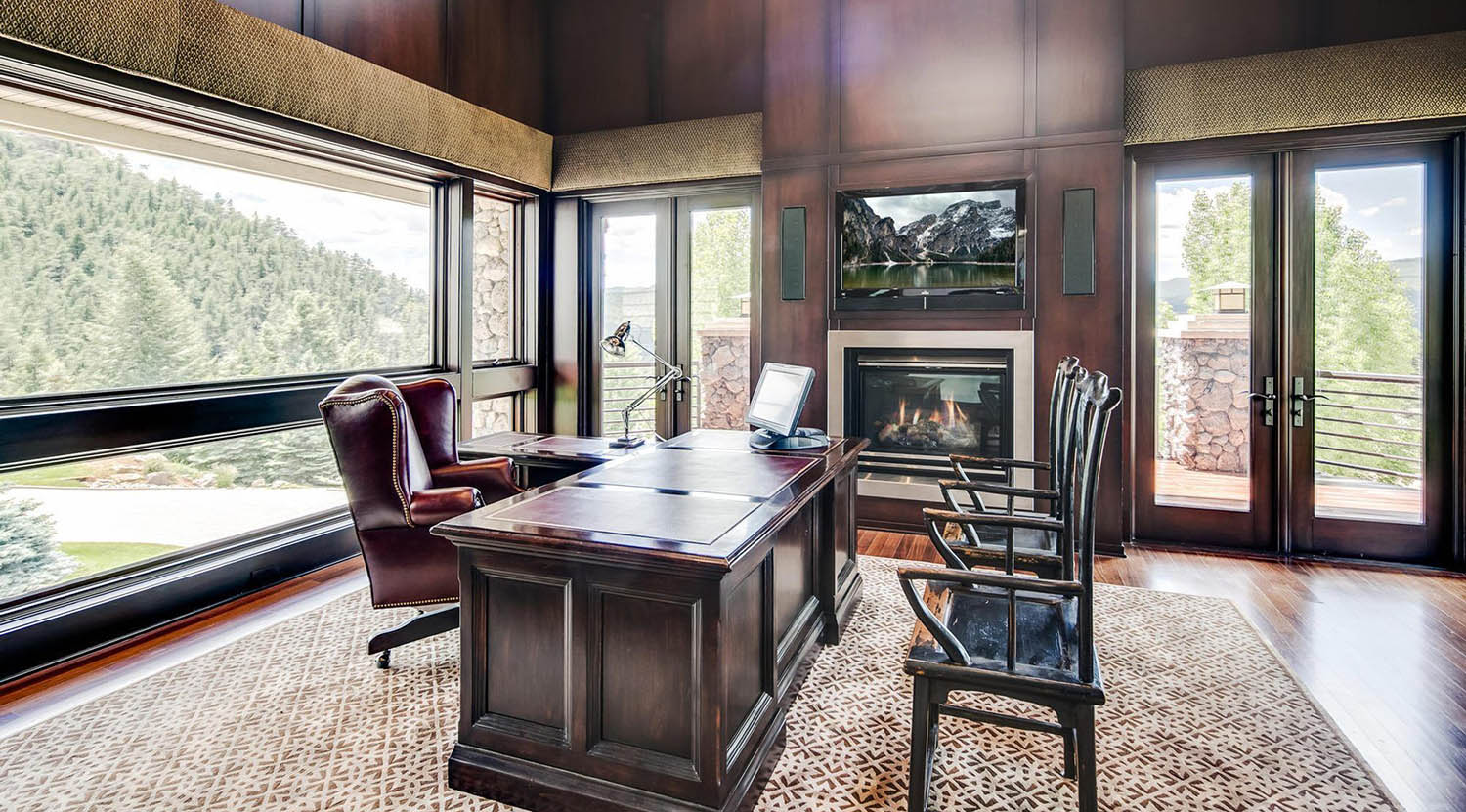 All wood wall paneling stained dark with matching wood desk. Huge windows let in tons of natural light. Built in gas fireplace.