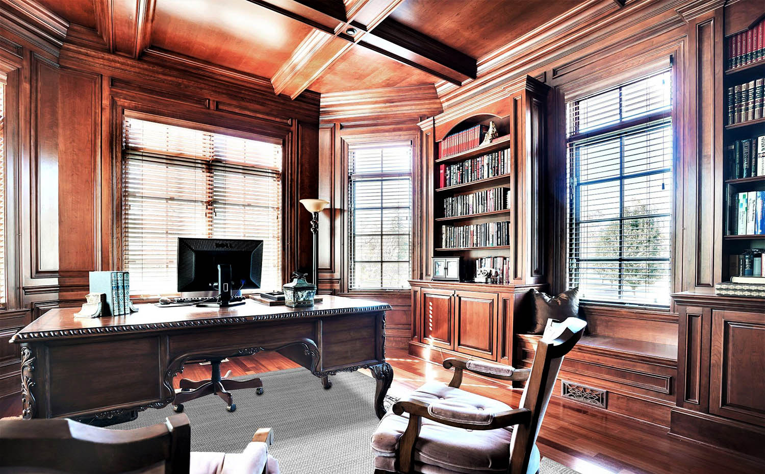 Beautiful home office with all wood walls and coffered ceiling stained medium brown. Hardwood floors with built ins.