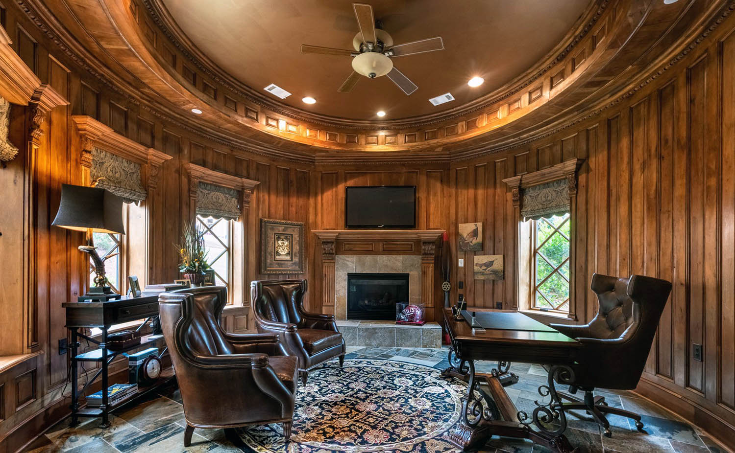 Round home office with wood wall panels and custom ceiling.