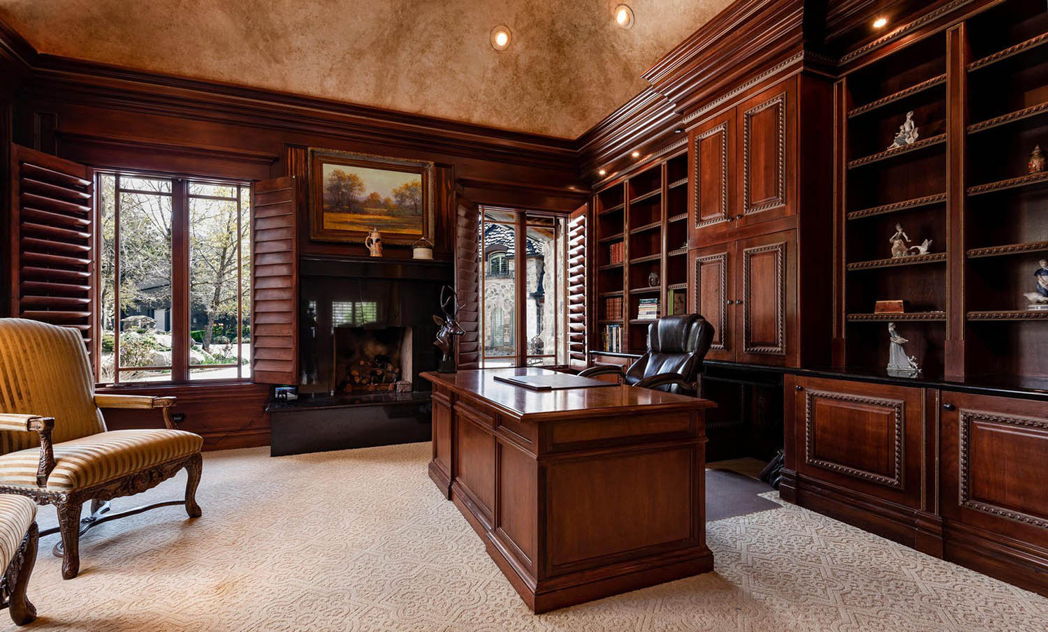 Home office with all wood wall panels and textured ceiling with built ins and cream carpet. Matching wood desk.