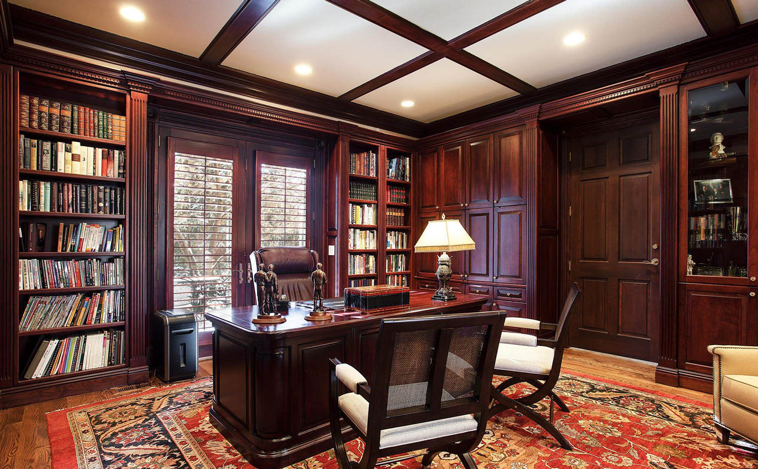Dark brown stained wood walls with built ins and matching wood desk.