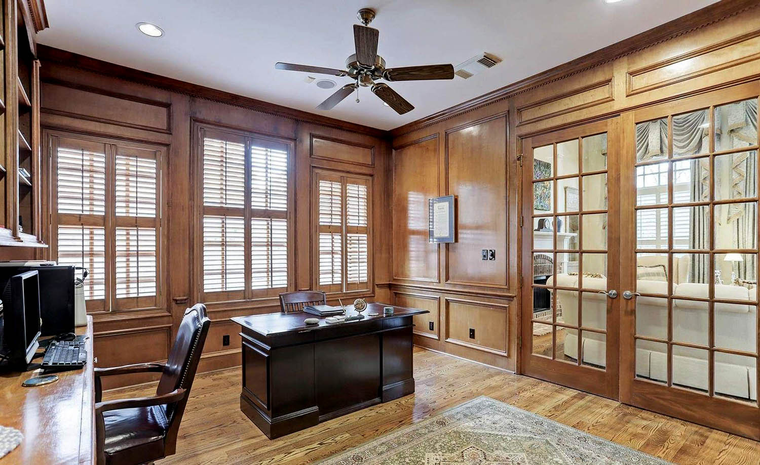 home office with light brown wood wall design and white ceiling. Contrasting dark brown wooden desk and chairs