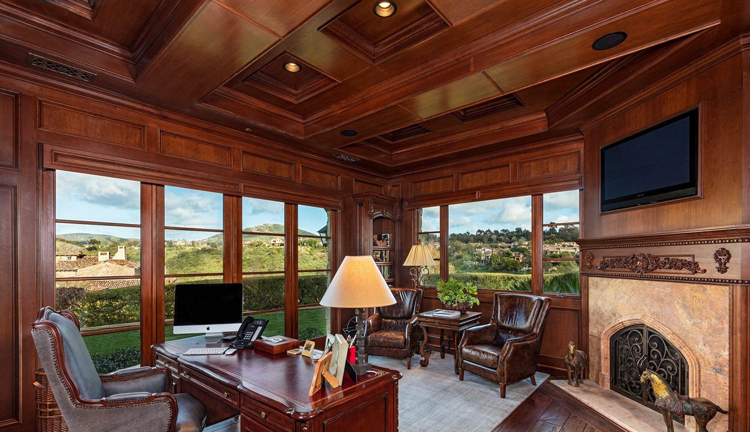 Home office with wood walls and custom trim. Built in wood burning fireplace. Hardwood floors and matching wood desk.