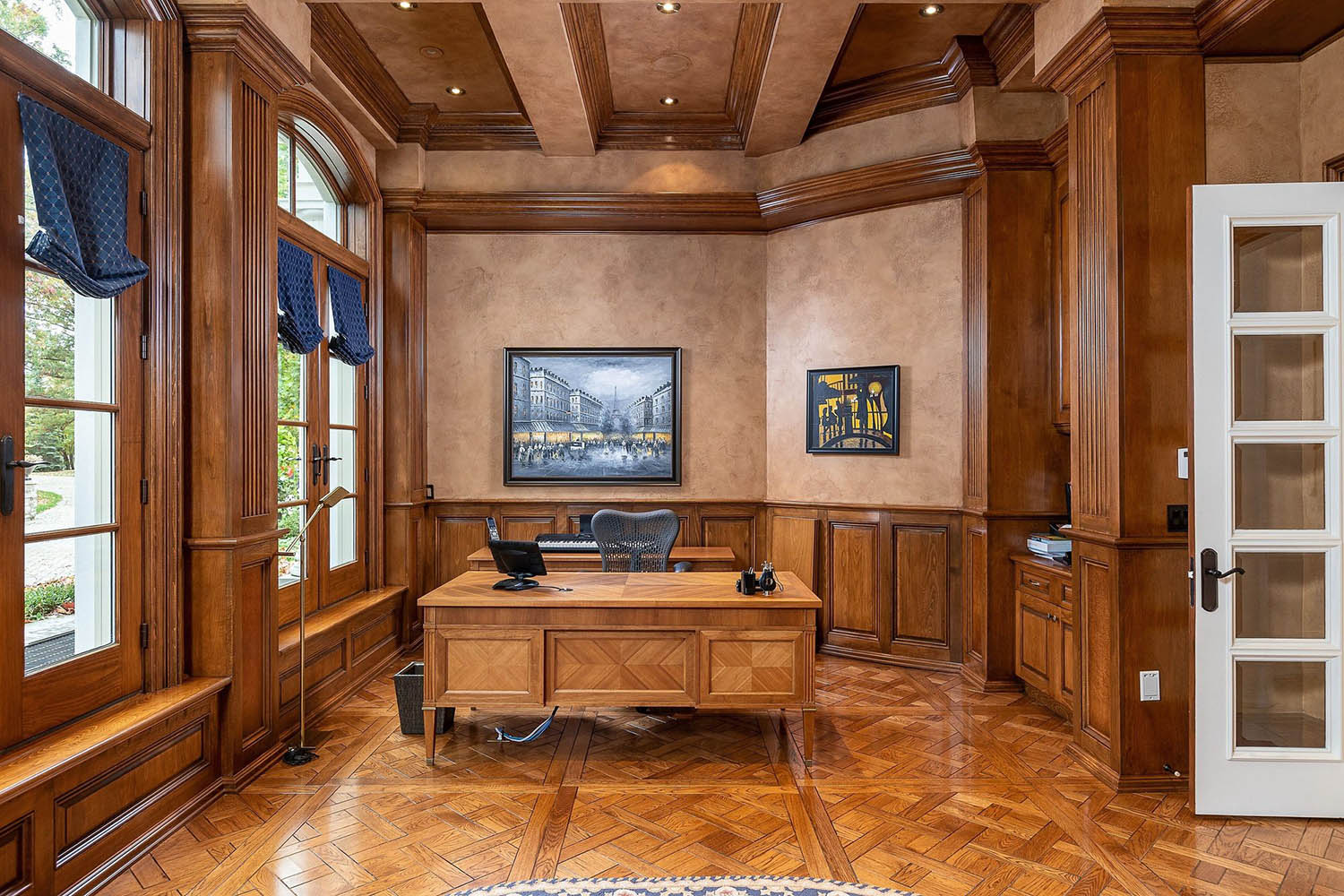 Home office with two toned wood walls. Lots of custom trim work and matching hardwood floors