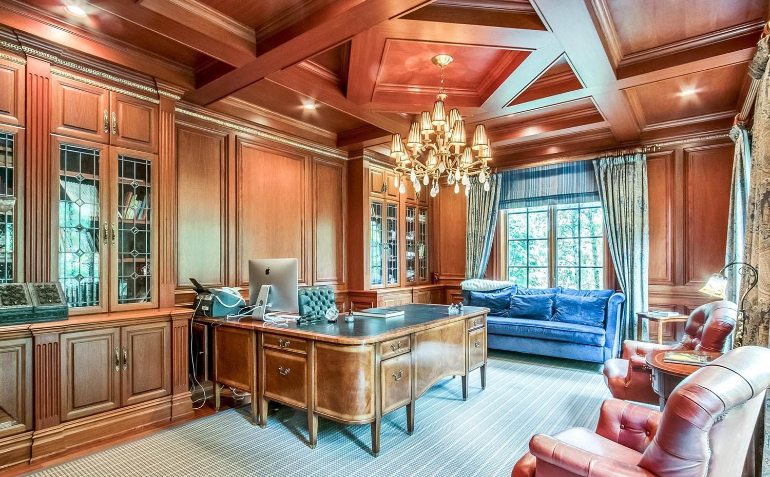 Home office with wood wall paneling and beautiful all wood coffered ceiling with center diamond design.