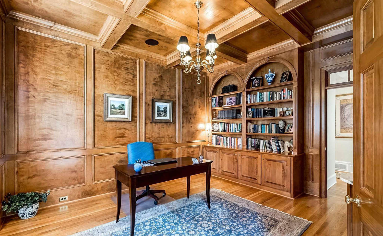 home office with all wood walls and dark brown desk, blue area rug, blue desk chair