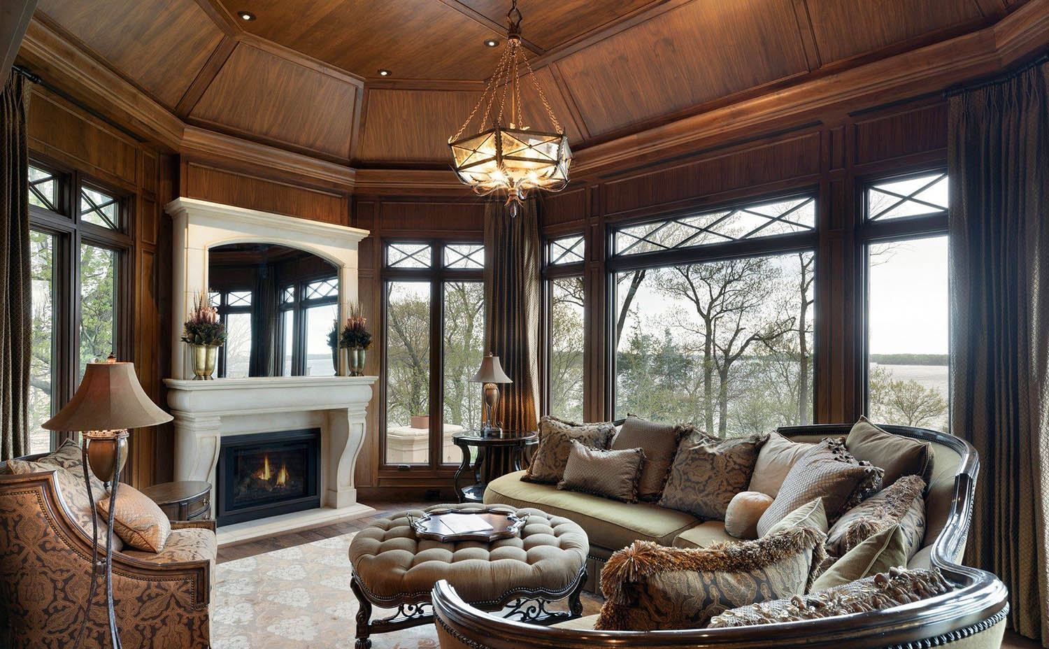 all wood walls sitting room with concrete fireplace surround tons of windows wood floors