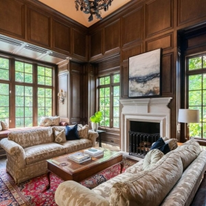 Beautiful sitting room with all wood wall panels and hardwood floors. Area rug. Cast fireplace surround.
